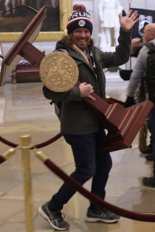 Guy stealing a podium from the Capitol