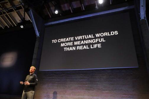 "Speaker in front of slide reading ""to create virtual worlds more meaningful than real life&quote."